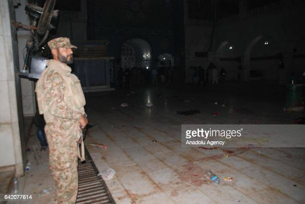 Pakistani army soldier stands alert at the site of a suicide attack at the 13th century old shrine of a Muslim saint in the town of Sehwan in...