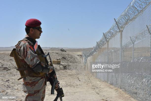 A Pakistani army soldier stands guard along with border fence at the PakAfghan border near the Punjpai area of Quetta in Balochistan on May 8 2018...