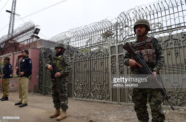 Pakistani army soldiers and policemen stand guard near the provincial assembly during the Senate election in Peshawar on March 3 2018 Pakistani...