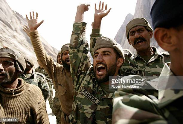 Pakistani Army soldiers cheer on one of their colleagues during a mountain training exercise near a battalion headquarters of the Pakistani Army at...
