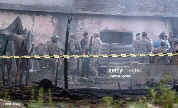 Pakistani army soldiers cordon off the the site of a plane crash an Rawalpindi, Pakistan on July 30, 2019. Fifteen people were killed when a Pakistan...