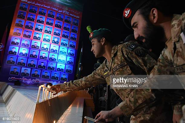 Pakistani army soldiers light candles in memory of the cadets killed at the Balochistan Police College in Quetta on October 29 2016 At least 62...