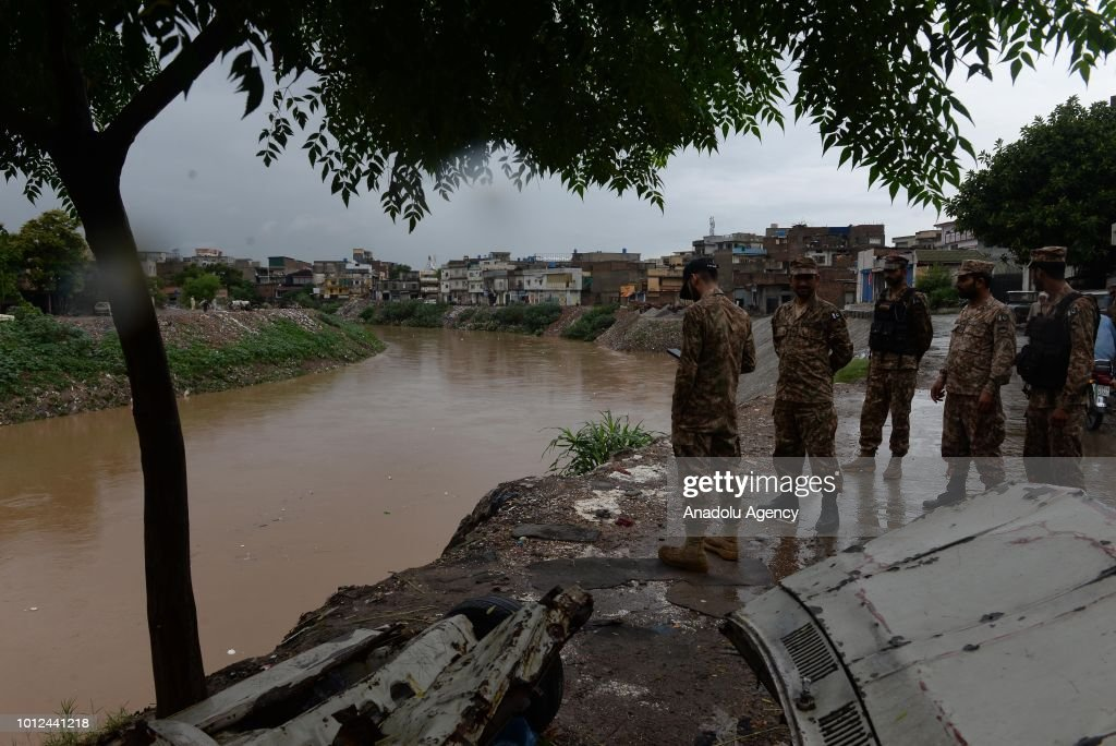 Pakistani army soldiers monitor the situation as they stand on the bank of a main stream after heavy monsoon rain hits the city of Rawalpindi...