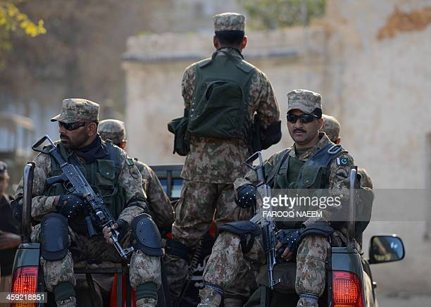 Pakistani army soldiers patrol as unseen Shiite Muslim mourners take part in a religious procession in Rawalpindi on December 24 2013 At least three...