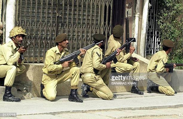 Pakistani army soldiers take position along a road in Quetta 04 July 2003 after a suicide attack at a Shiite Muslim mosque during the Friday noon...