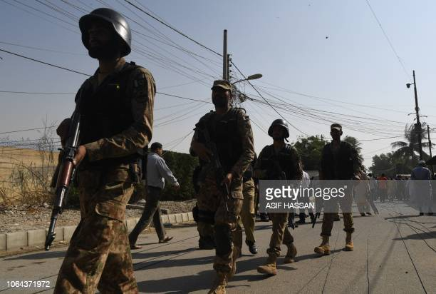 Pakistani army soldiers walk outside the Chinese consulate after an attack in Karachi on November 23 2018 At least two policemen were killed when...