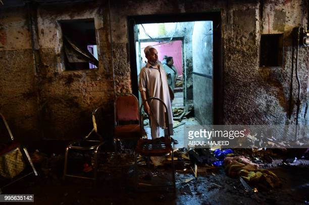 A Pakistani Awami National Party supporter stands at the site after a suicide bombing at an election rally in Peshawar on July 10 2018 A suicide...