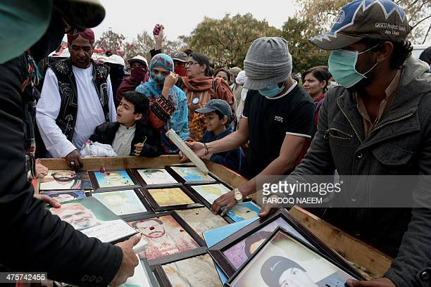 Pakistani Baloch activists arrange pictures of missing persons at the start of a rally at the conclusion of a 2000 km march led by Mama Qadir in...