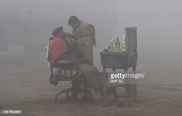 Pakistani barber shaves a customer alongside a road amid heavy fog and smog conditions in Lahore on January 24 2019 Smog levels spike during winter...