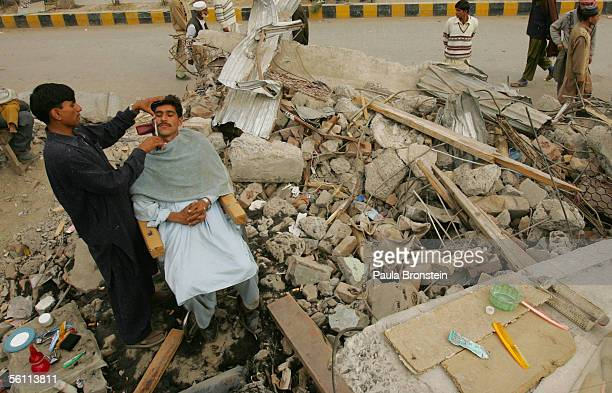 Pakistani barber shaves a man's face in his open air shop sitting amongst the rubble as life attempts to get back to normal November 7 2005 in...