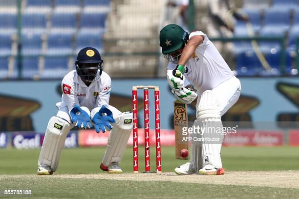 Pakistani batsman Azhar Aki plays a shot as Sri Lankan wicketkeeper Niroshan Dickwella looks on during the third day of the first Test cricket match...