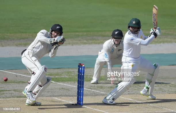 Pakistani batsman Azhar Ali plays a shot as New Zealand wicketerkeeper BJ Watling and teammate Henry Nicholls look on during the first day of the...