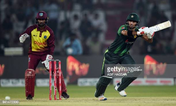 Pakistani batsman Hussain Talat is watched by West Indies wicketkeeper Denesh Ramdin as he plays a shot during the third and final Twenty20...