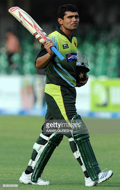 Pakistani batsman Kamran Akmal raises his bat as he leaves the ground after being dismissed during the third One-Day International cricket match...
