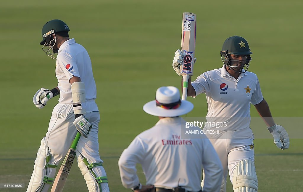 Pakistani batsman Sami Aslam (R) raises his bat after scoring 50 runs on the third day of the second Test between Pakistan and the West Indies at the Sheikh Zayed Cricket Stadium in Abu Dhabi on October 23, 2016. Openers Azhar Ali and Sami Aslam hit half-centuries to help Pakistan strenghten their grip on the third day of the second Test against West Indies in Abu Dhabi. Ali was batting on 52 and Asad Shafiq five not out to take Pakistan to 114-1, having an overall lead of 342 after dismissing West Indies for 224 in their first innings. / AFP / AAMIR