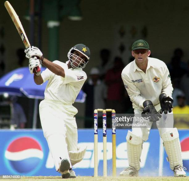 Pakistani batsman Taufiq Umar plays a lofted shot for four as Australian wicketkeeper Adam Gichrist looks on during the 4th day's play of the first...