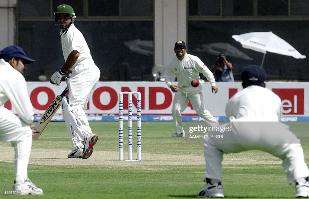 Pakistani batsman Taufiq Umer (2-L), Indian players Venkatsai Laxman (L) and Sachin Tendulkar (2-R) look on as Rahul Dravid bends forward to take a catch off Indian bowler Irfan Pathan (not in picture) during the third dayS play of the first Test match between Pakistan and India in Multan, 30 March 2004. Chasing India's first inning's score of 675 runs, Pakistan made 252 for the loss of four wickets at tea break. AFP PHOTO / Aamir QURESHI