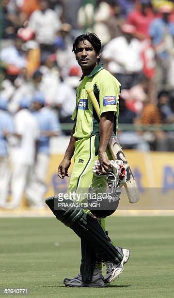Pakistani batsman Yousuf Youhana leaves the pitch after being run out for 50 during the final one day international between India and Pakistan at...