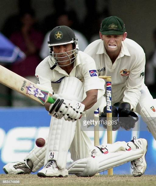 Pakistani batsman Yunis Khan sweeps a ball as Australian wicketkeeper Adam Gilchrist looks on during the final day of the first cricket Test match...