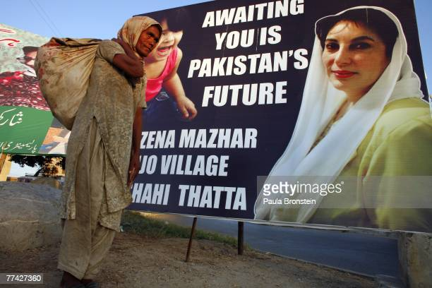 Pakistani beggar walks by a Bhutto poster two days after two explosions killed at least 134 people and wounded 450 during an assasination attempt on...