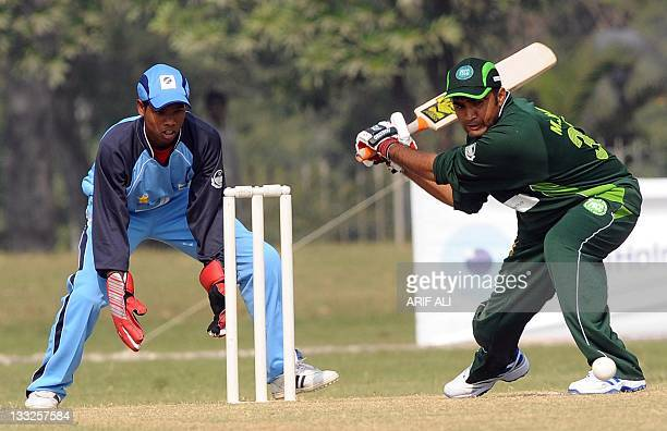 Pakistani blind cricketer Muhammad Jamil plays a shot as Indian blind wicketkeeper Prakash Jayaramaiah stands in position during the first...