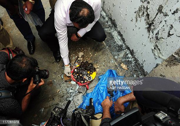 Pakistani bomb disposal squad officials examine diffused bomb material outside the building of the International Committee of Red Cross in Karachi on...