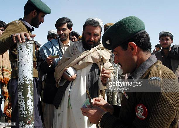 Pakistani border security guards check the documents of Afghans crossing into Pakistan from Afghanistan at the Chaman border crossing March 17 2003...