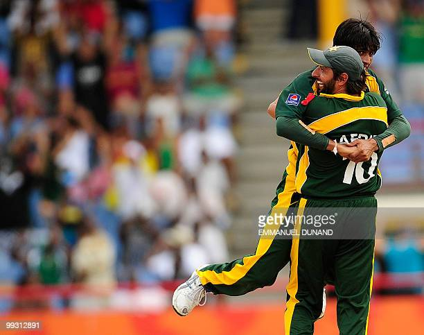 Pakistani bowler Mohammad Aamer celebrates with captain Shahid Afridi after taking the wicket of Australian batsman Cameron White during the ICC...