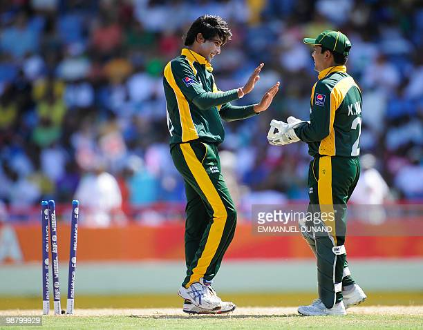Pakistani bowler Mohammad Aamer celebrates with wicketkeeper Kamran Akmal after taking the wicket of Australian batsman Mitchell Johnson during the...