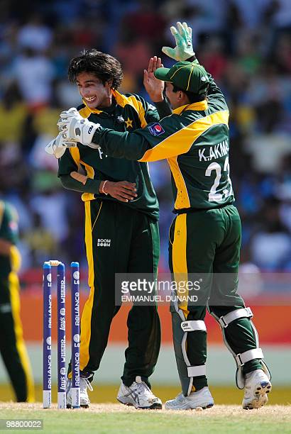 Pakistani bowler Mohammad Aamer celebrates with wicketkeeper Kamran Akmal after taking the wicket of Australian batsman Tim Paine during the ICC...