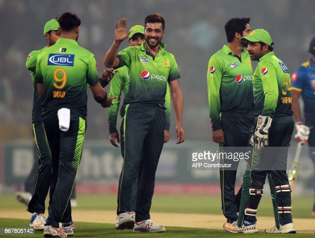 Pakistani bowler Mohammad Amir celebrates with teammates after dismissing Sri Lankan batsman Dilshan Munaweera during the third and final T20 cricket...