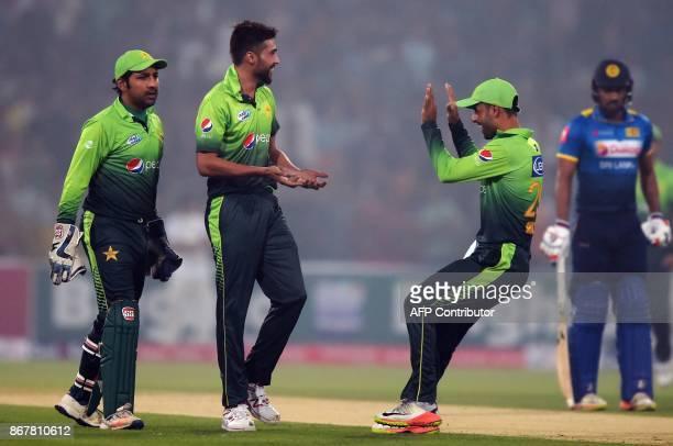 Pakistani bowler Mohammad Amir celebrates with teammates Shadab Khan and wicketkeeper Sarfraz Ahmad after dismissing Sri Lankan batsman Dilshan...