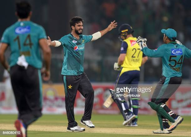 Pakistani bowler Rumman Raees celebrates with teammates after taking the wicket of World XI batsman Tamim Iqbal during the first Twenty20...