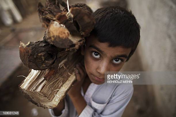 Pakistani boy Arsalan carries home wood to be used for cooking in a poor neighborhood of Islamabad on July 21 2010 Pakistan with almost 170 million...