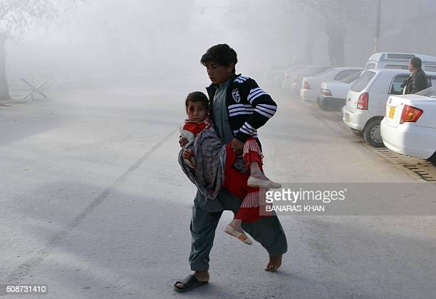 Pakistani boy carries an injured girl from the site of a bomb explosion that targeted a security convoy in Quetta on February 6 2016 A bomb blast...