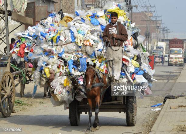 Pakistani boy carries waste plastic bags on a horsedriven cart in Lahore on December 11 2018
