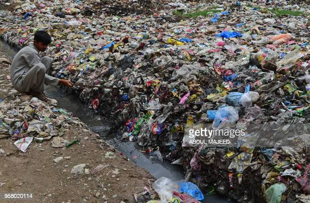 Pakistani boy clears a sewerage line at a rubbish dump filled with plastic items in Peshawar on May 13 2018