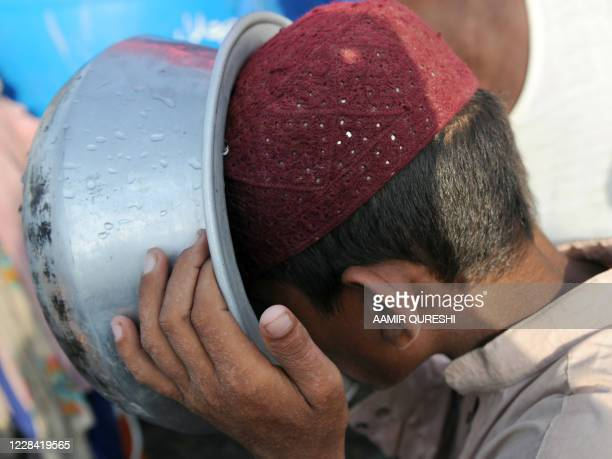 Pakistani boy displaced by floods drinks water as he waits for food at a makeshift camp in Sukkur, in the southern province of Sindh, on September 8,...