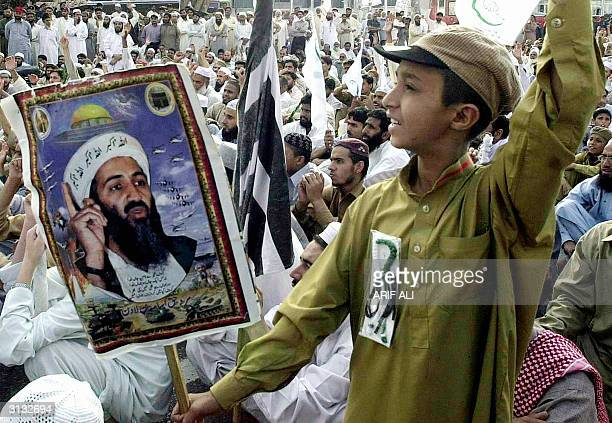 Pakistani boy holds a poster of Al Qaeda chief Osama bin Laden as he shouts anti-US slogans during a demonstration organised by a Mutahida...