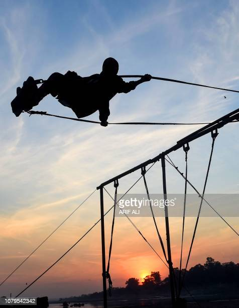A Pakistani boy plays on the swings at sunset in Lahore on January 9 2019
