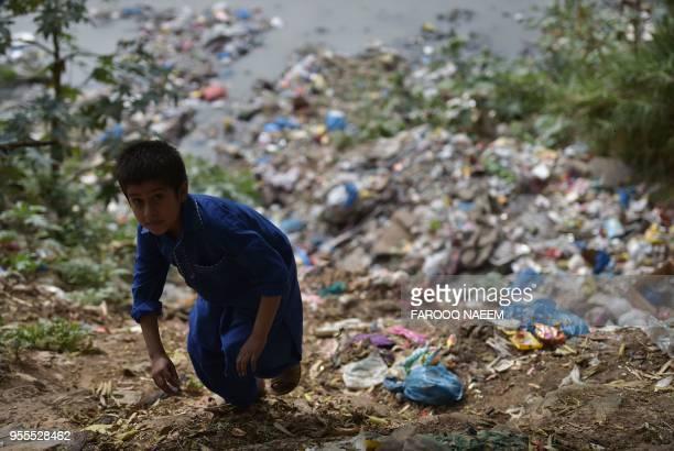 A Pakistani boy walks beside plastic bags dumped alongside a stream in Rawalpindi on May 5 2018