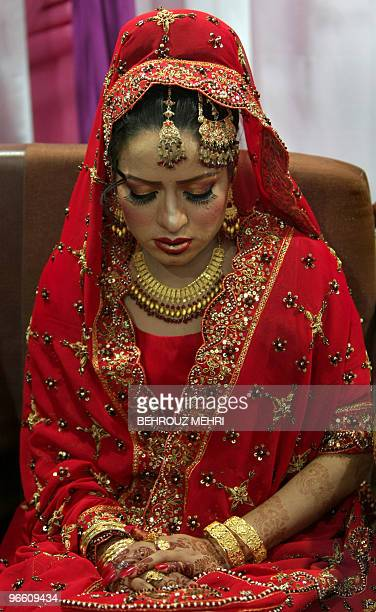 Pakistani bride Najma Khalil folds her hands decorated with henna and jewellery while wearing the Lehenga wedding cloth at her wedding party in...