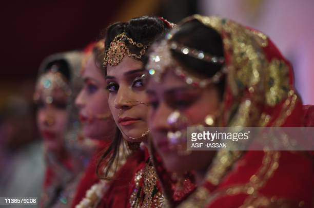 Pakistani brides attend their a mass-wedding ceremony in Karachi on April 13, 2019. - Dozens of couples who could not afford their individual wedding...