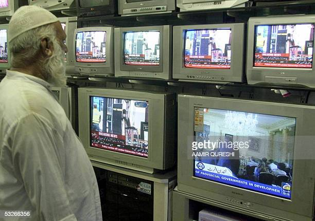 Pakistani bystander watches a bank of televisions in an electronic shop in Karachi, 21 July 2005. Showing a news channels coverage of recent bomb...