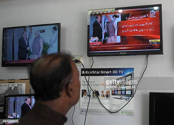 A Pakistani bystander watches televisions in a showroom of an electronic market in Karachi on May 27 as they display images of India's Prime Minister...
