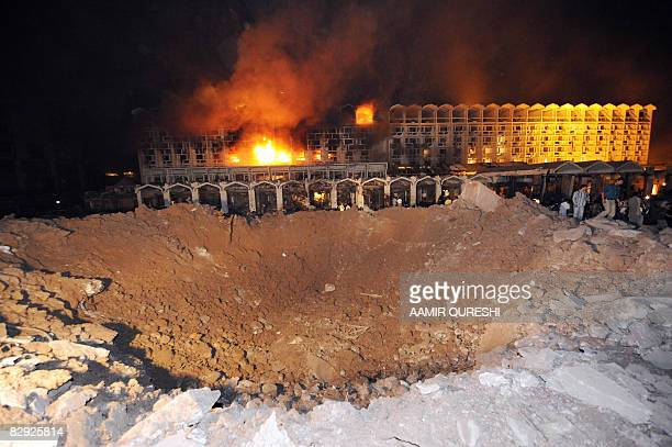 Pakistani bystanders and rescue workers are seen beside a huge crater outside the burning facade of The Marriott Hotel in Islamabad on September 20...