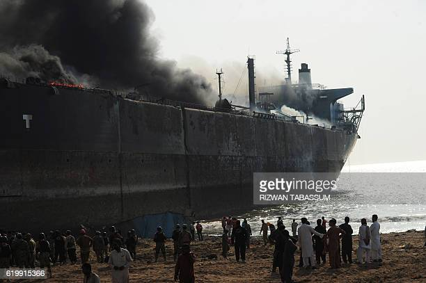Pakistani bystanders gather around the wreckage of a burning ship after a gas cylinder explosion at the Gadani shipbreaking yard some 50 kilometres...