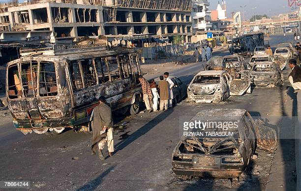 Pakistani bystanders look at the burnt out wreckage of vehicles set on fire by supporters of former Pakistani prime minister Benazir Bhutto in...