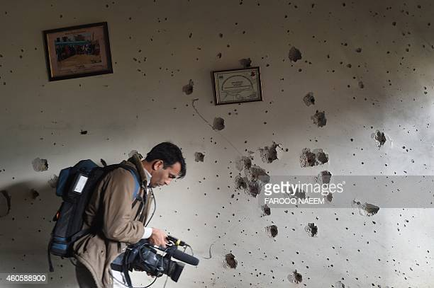 A Pakistani camera man shoots video in front of a bulletriddled wall at the arm run school a day after an attack by Taliban militants in Peshawar on...