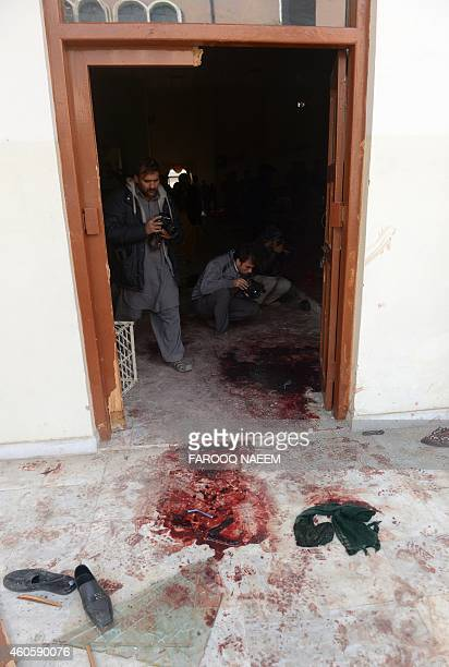 A Pakistani cameraman shoots the bloodied floor at an armyrun school a day after an attack by Taliban militants in Peshawar on December 17 2014...